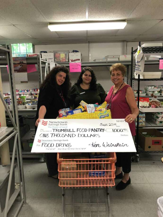 Newtown Savings Bank employees Carissa Costello and Priscila Otoni Rodrigues bring food drive donations and a $1,000 check to the Trumbull Food Pantry to serve families in need. Karen Seferi also in photo, Food Pantry Coordinator. Photo: Contributed Photo