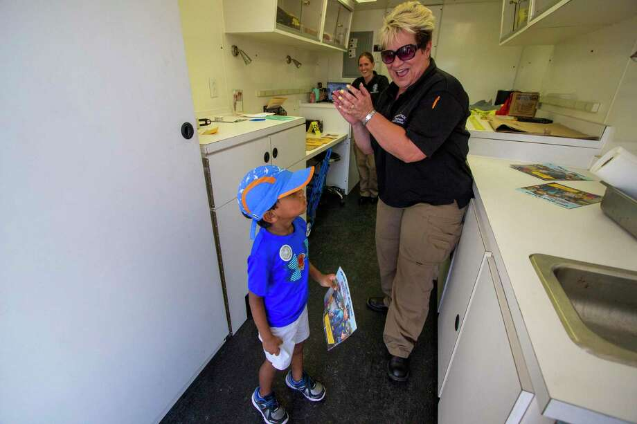 Yehen Kaggoda, left, points out that he could brush his teeth using the sink in the Conroe Police Department Crime Scene mobile unit during National Night Out on October 1, 2019 at Kroger Marketplace in Conroe. Jacqueline Gray laughs and cheered him on as she finished showing him the unit. Photo: Cody Bahn, Houston Chronicle / Staff Photographer / © 2019 Houston Chronicle