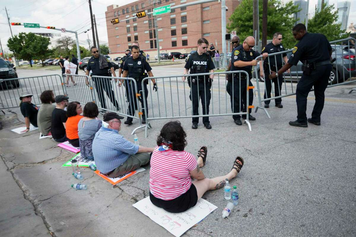 Police officers put up barricades around protestors sitting in front of the entrance of the Southwest Key facility on Emancipation Ave, in Houston in July.