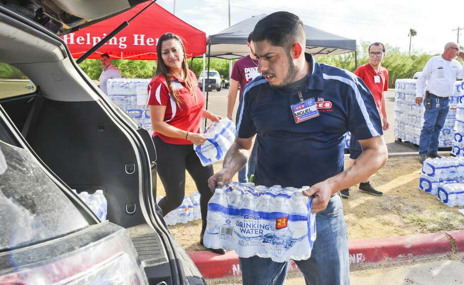 H-E-B employees Yvonne Loflin and Miguel Valdez load vehicles with cases of waters donated by H-E-B to Laredoans living in the areas under a boil water notice, Tuesday, Oct. 1, 2019, at Independence Hills park. Photo: Danny Zaragoza/Laredo Morning Times