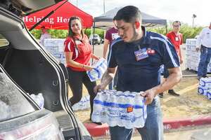 H-E-B employees Yvonne Loflin and Miguel Valdez load vehicles with cases of waters donated by H-E-B to Laredoans living in the areas under a boil water notice, Tuesday, Oct. 1, 2019, at Independence Hills park.