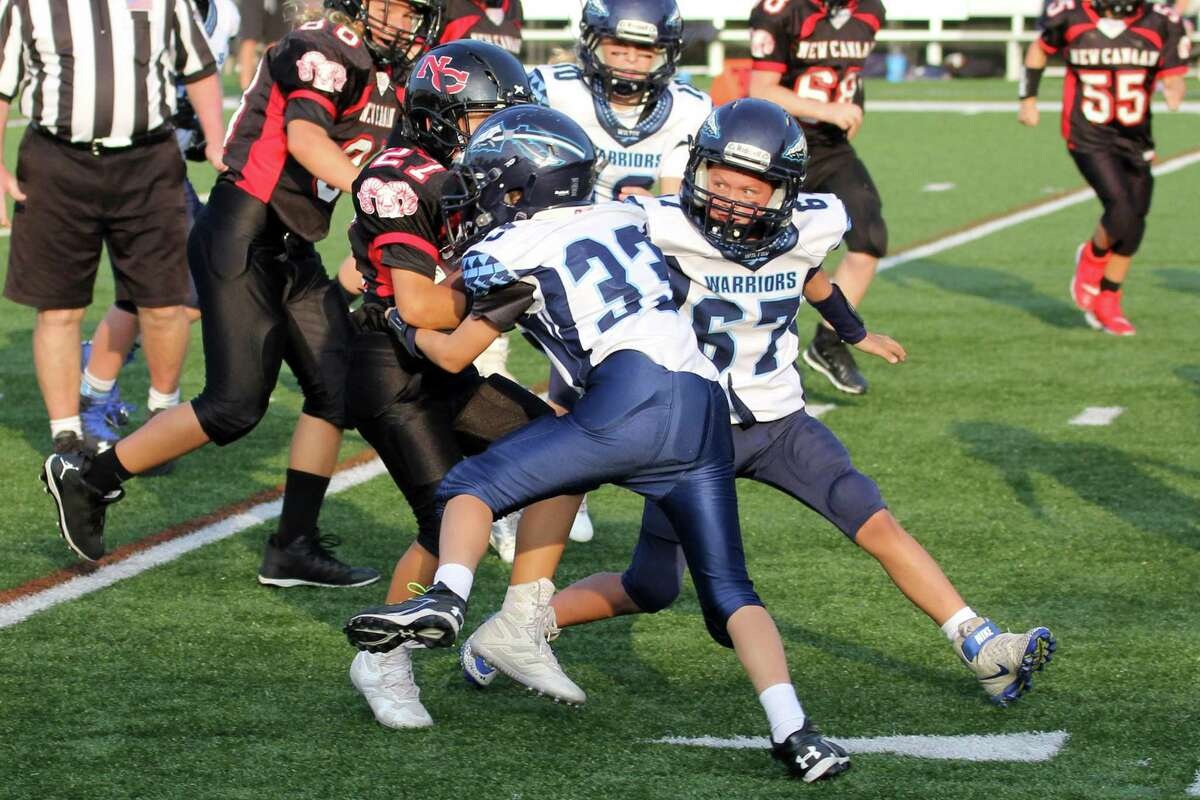 Wilton's Will Byrnes (#33) makes a tackle with help from teammates Evan Christianson (#67) and Emma Van Heyst (#10) during a 6th Grade youth football game.