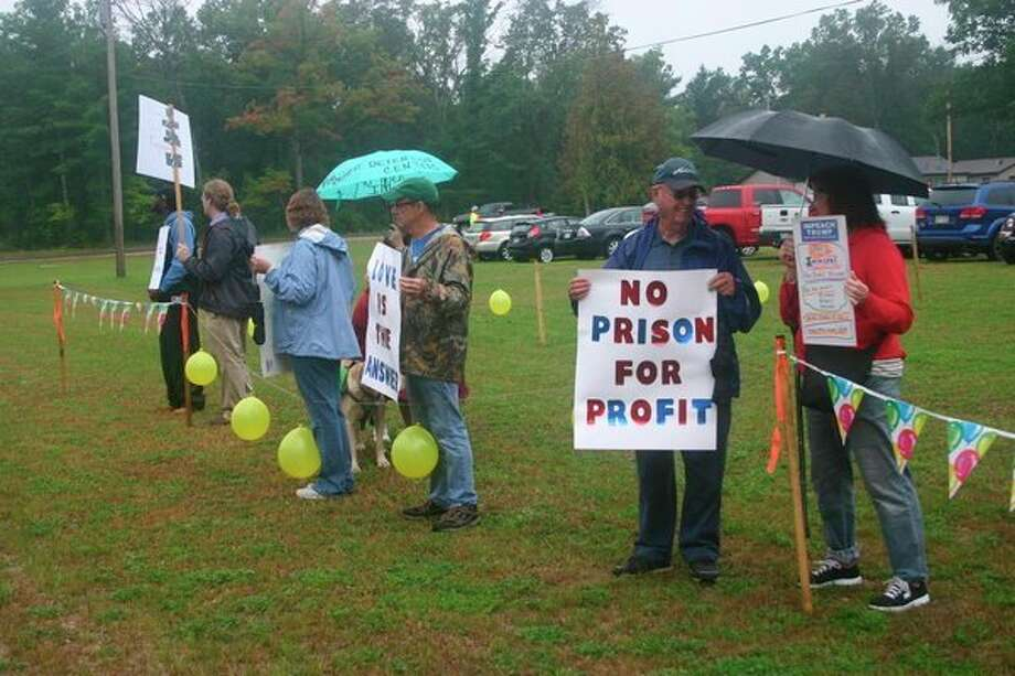 Lake County Democratic Party members join the protest against the opening of North Lake Correctional facility on Tuesday, Oct. 1 in Baldwin. Despite the weather, protesters hung around to show their opposition to the facility. (Star photo/Cathie Crew)