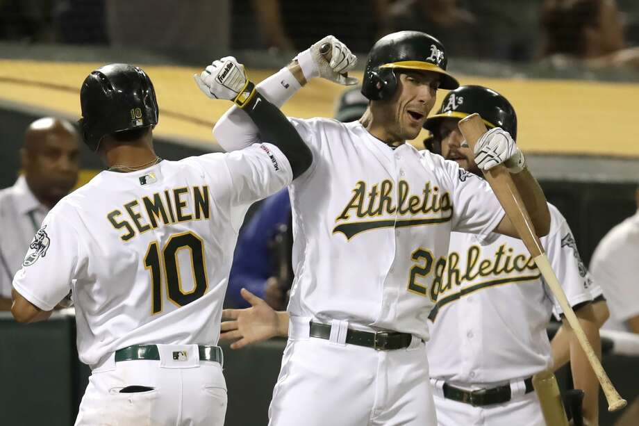 Oakland Athletics' Marcus Semien (10) celebrates with Matt Olson, right, after hitting a home run against the Texas Rangers during the fifth inning of a baseball game Saturday, Sept. 21, 2019, in Oakland, Calif. (AP Photo/Ben Margot) Photo: AP Images / Copyright 2019 The Associated Press. All rights reserved.