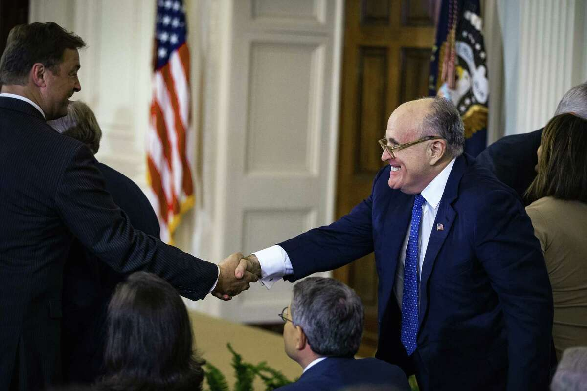 Rudy Giuliani, former mayor of New York (right) shakes hands on July 9, 2018 with then-Sen. Dean Heller, R-Nev., in the East Room of the White House in Washington.
