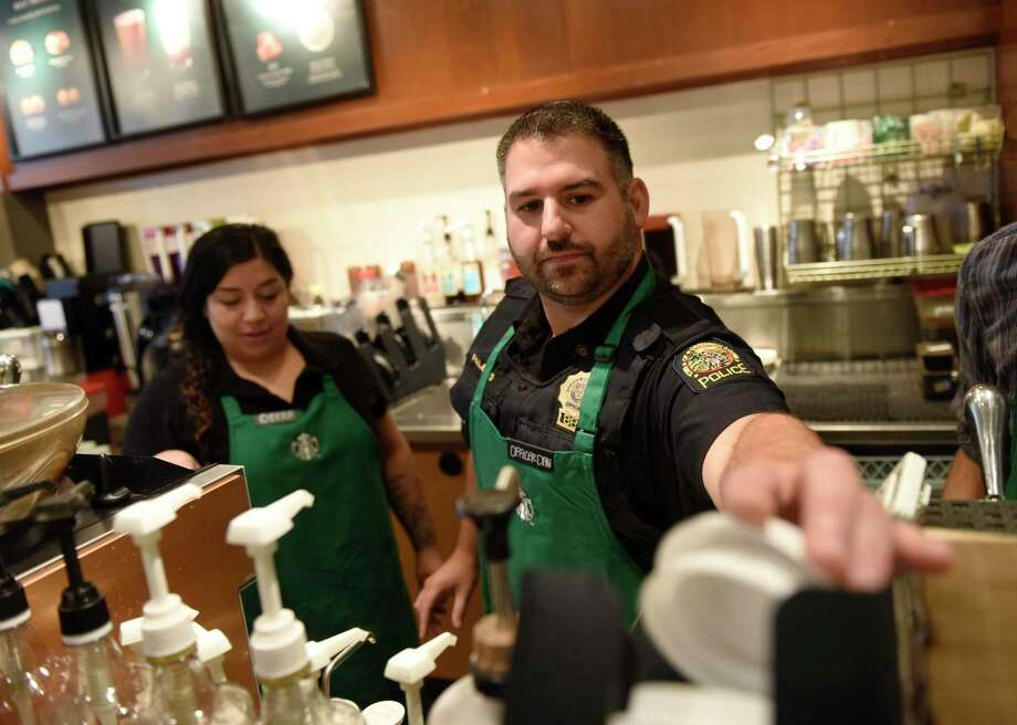 Greenwich Police Officer Dan Paladino makes drinks at the bar during the Coffee with a Cop event at Starbucks in the Riverside section of Greenwich on Wednesday. The event allowed citizens to chat with Greenwich police officers in a casual setting to give them a feel for the men and women behind the uniforms. Photo: Tyler Sizemore / Hearst Connecticut Media / Greenwich Time