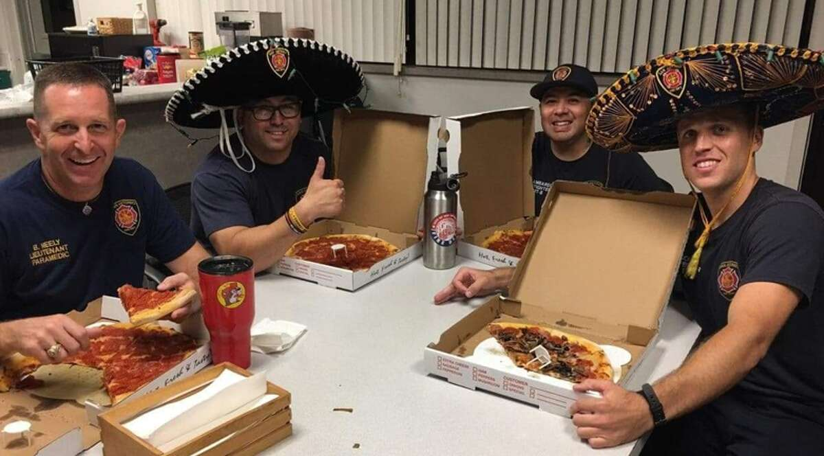 San Antonio Fire Department firefighters enjoying the accidental Alamo Pizza from their fellow firefighters in Canada.
