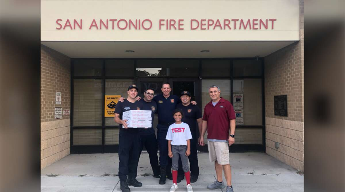 Alamo Pizza owner Fred Nunez (right) and his step-daughter (front) delivering pizzas to San Antonio Fire Department firefighters that were accidentally ordered by the Lesser Slave Regional Fire Service in Canada. After realizing the Google mistake that directed their order for