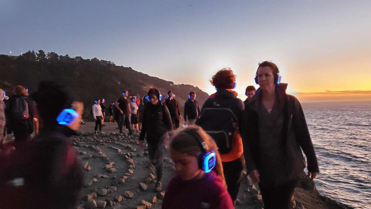 Bay Area locals hike through Land's End with wireless headphones as part of a silent hike series put on by composer Murray Hidary.