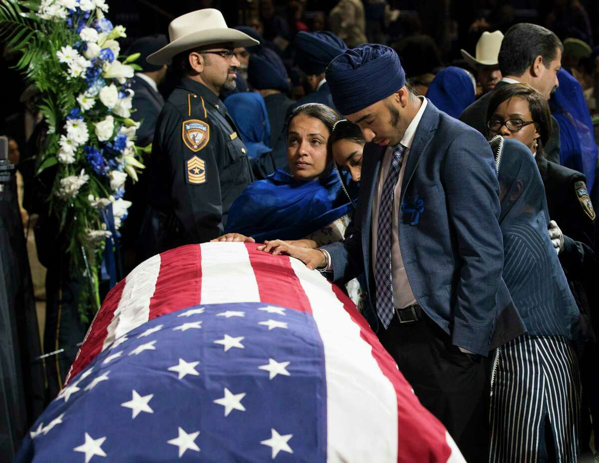 A mourner touches the casket of Harris County Sheriff's Deputy Sandeep Dhaliwal during his funeral at Berry Center on Wednesday, Oct. 2, 2019, in Houston. Dhaliwal was killed in the line of duty Friday, when he was shot and killed during a traffic stop.