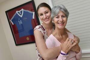 Kyley Reed, left, with her mother, Dorothy Franco-Reed, at her mother's home in Milford on Sept. 12, 2019. In the background is Franco-Reed's jersey from the 1984 Olympic handball team.