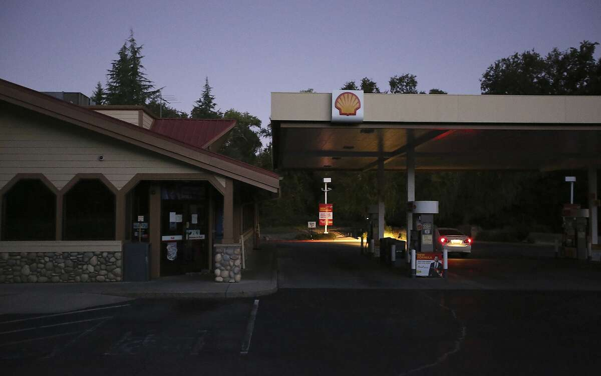 In this Wednesday morning, Sept. 24, 2019 photo, a gas station in Penn Valley, Calif. sits dark as motorists check to see if the pumps were working. Pacific Gas & Electric has shut off power to 24,000 customers in the Sierra Nevada foothills and says it will remain off until dangerous wildfire weather eases. (Elias Funez/The Union via AP)