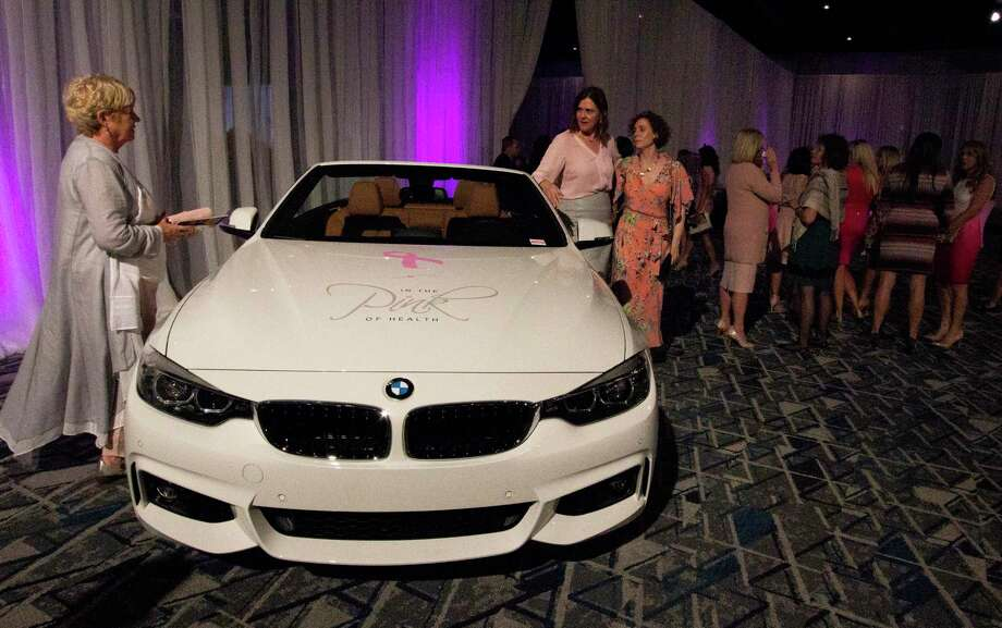 Guests take a look at a BMW convertible, which was up for raffle, during last year's In the Pink of Health luncheon hosted by Memorial Hermann Health System at The Woodlands Waterway Marriott Hotel & Convention Center. This year's In the Pink of Health event will take place on Oct. 18, also at The Woodlands Waterway Marriott Hotel. Photo: Cody Bahn, Houston Chronicle / Staff Photographer / © 2018 Houston Chronicle
