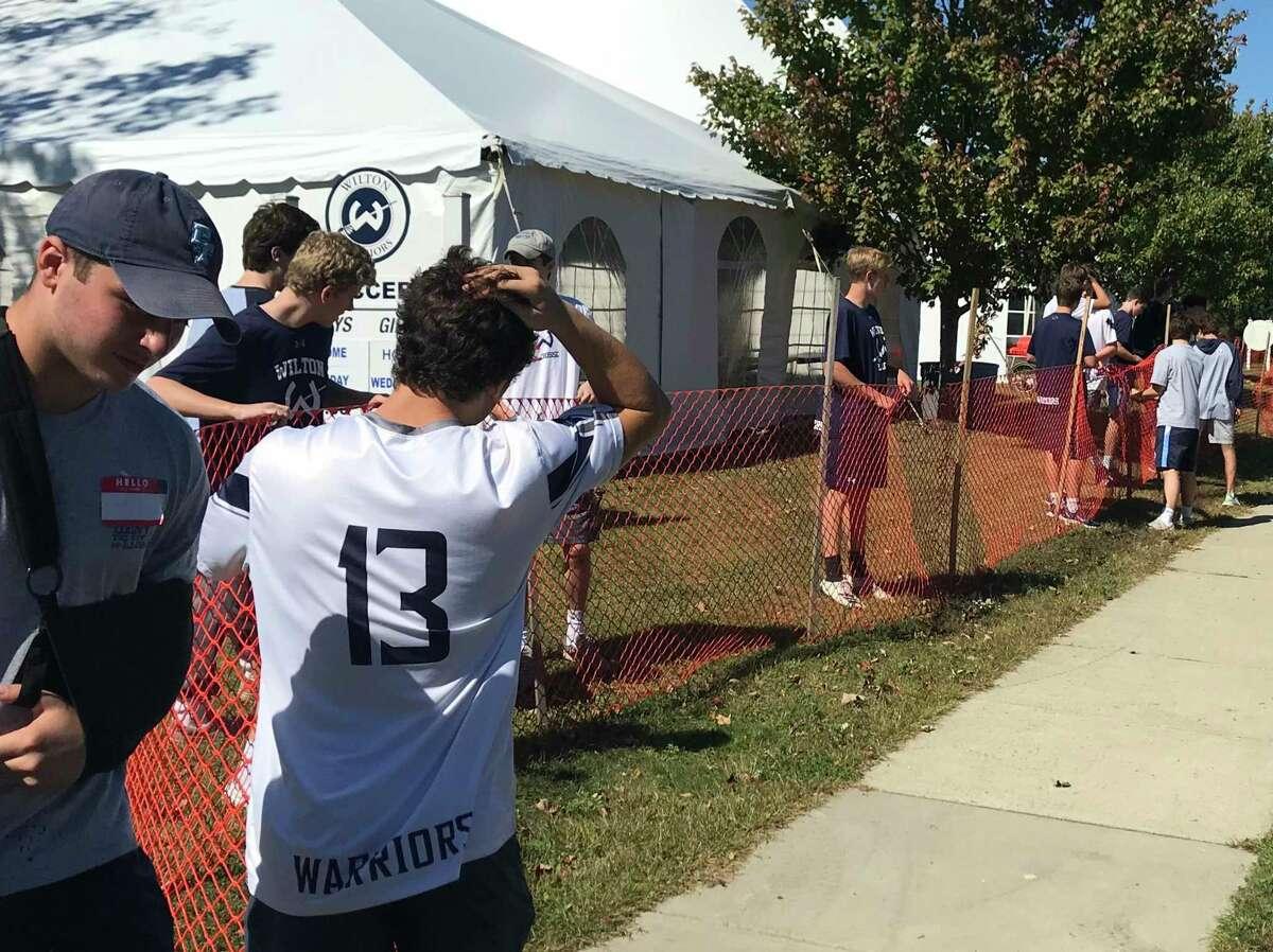 Members of Wilton High School's boys lacrosse teams help Minks to Sinks volunteers set up the weekend of Sept. 28-29.