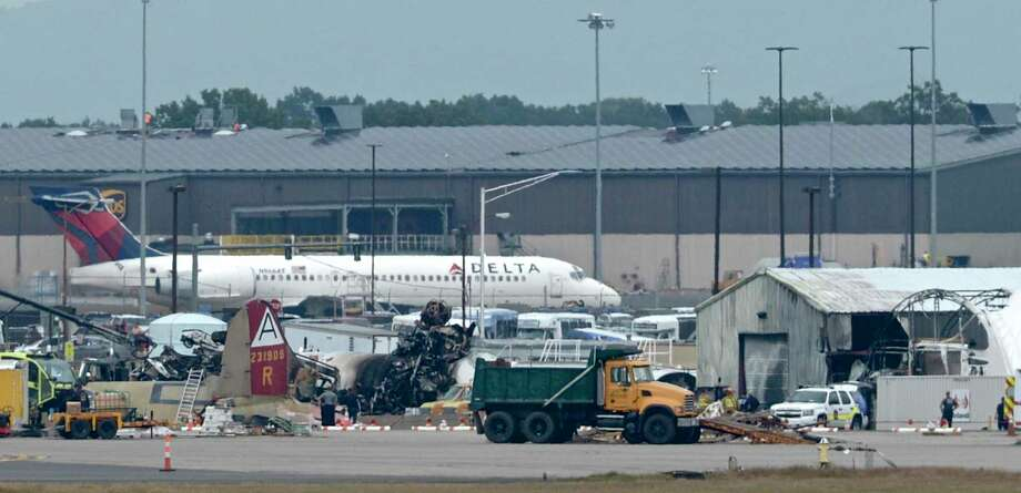 A vintage WWII aircraft wreckage lays off a runway at Bradley International Airport in Windsor Locks, Conn, on Wednesday morning. The aircraft crashed as it attempted to land after reporting trouble. The aircraft was reported to have three crew members and 10 passengers aboard and officials have confirmed multiple fatalities in the Wednesday morning crash. Wednesday, October 2, 2019. Photo: H John Voorhees III / Hearst Connecticut Media / The News-Times