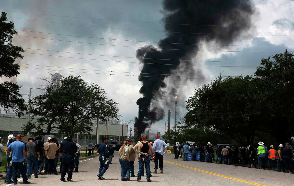 Evacuated Exxon Mobil workers on July 31, 2019, watch the fire from the Baytown Olefins Plant entrance in Baytown, Texas. Harris County will hire more environmental personnel for better response to dangerous chemical plant and refinery fires like several accidents this year near the Houston Ship Channel.