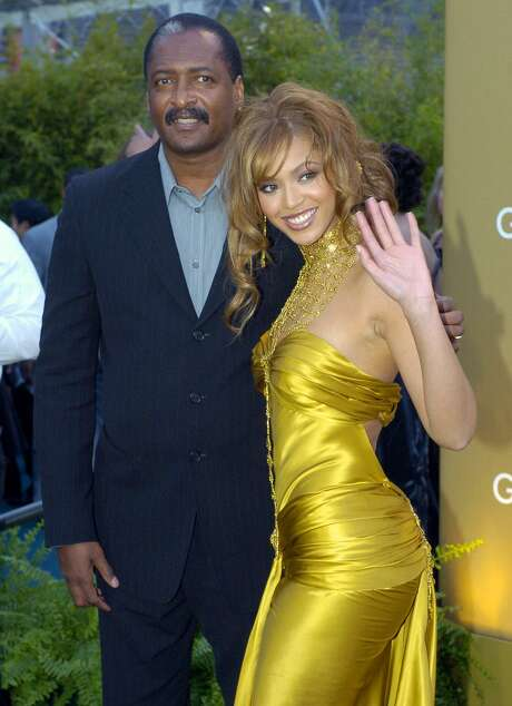In this Feb. 8, 2004, file photo, singer Beyonce Knowles arrives at the 46th Annual Grammy Awards with her father and manager Mathew Knowles in Los Angeles.