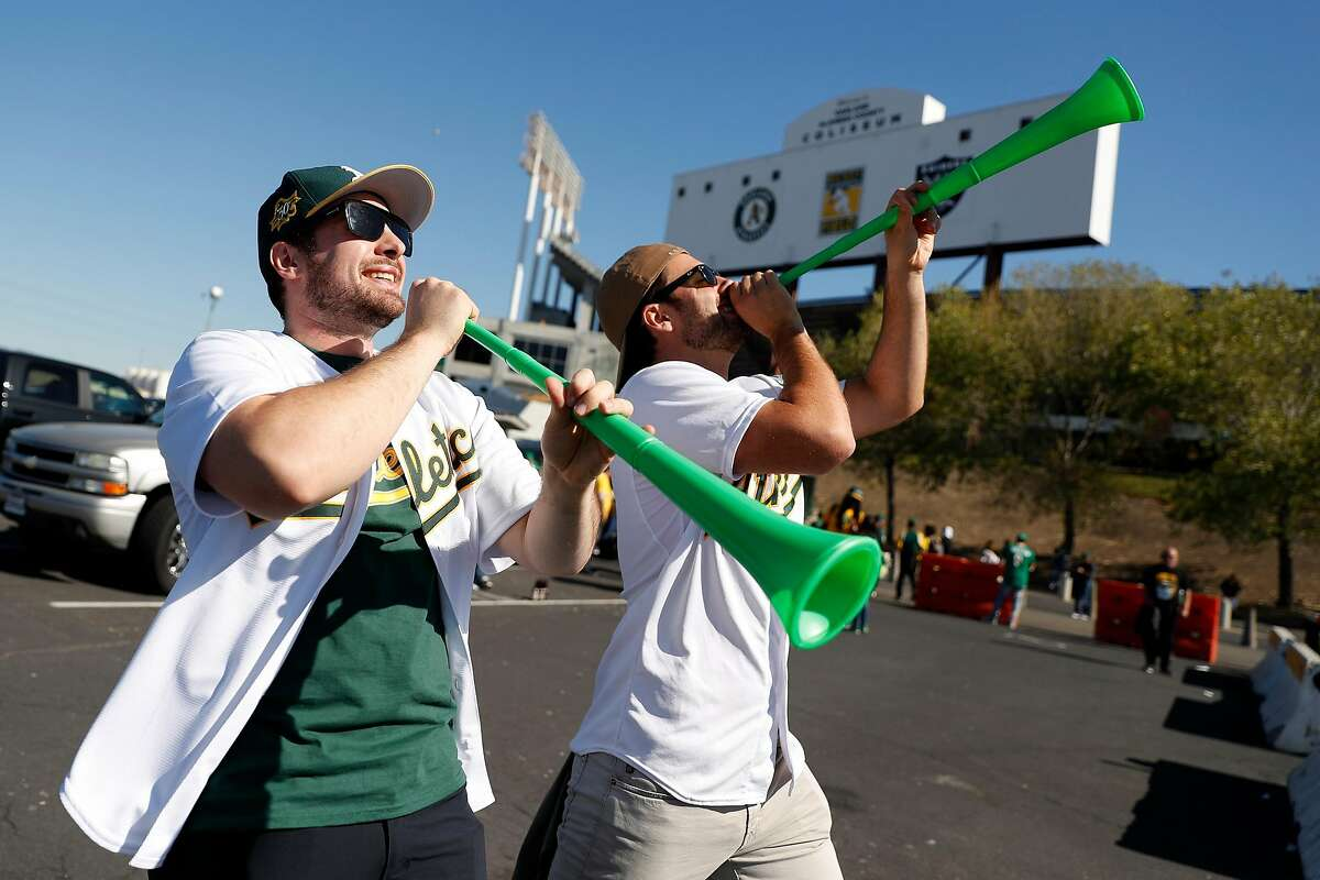 Brothers and Oakland Athletics' fans, Dylan and Evan Dreyer of Sacramento blow horns before Oakland Athletics play Tampa Bay Rays in American League Wild Card game at Oakland Coliseum in Oakland, Calif., on Wednesday, October 2, 2019.