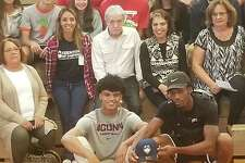 Andre Jackson shows off his UConn T-shirt after giving his oral commitment to the University of Connecticut. He father, also Andre Jackson, holds up a UConn hat, and both are surrounded by friends and family at Albany Academy on Wednesday, Oct. 2, 2019. (James Allen / Times Union)