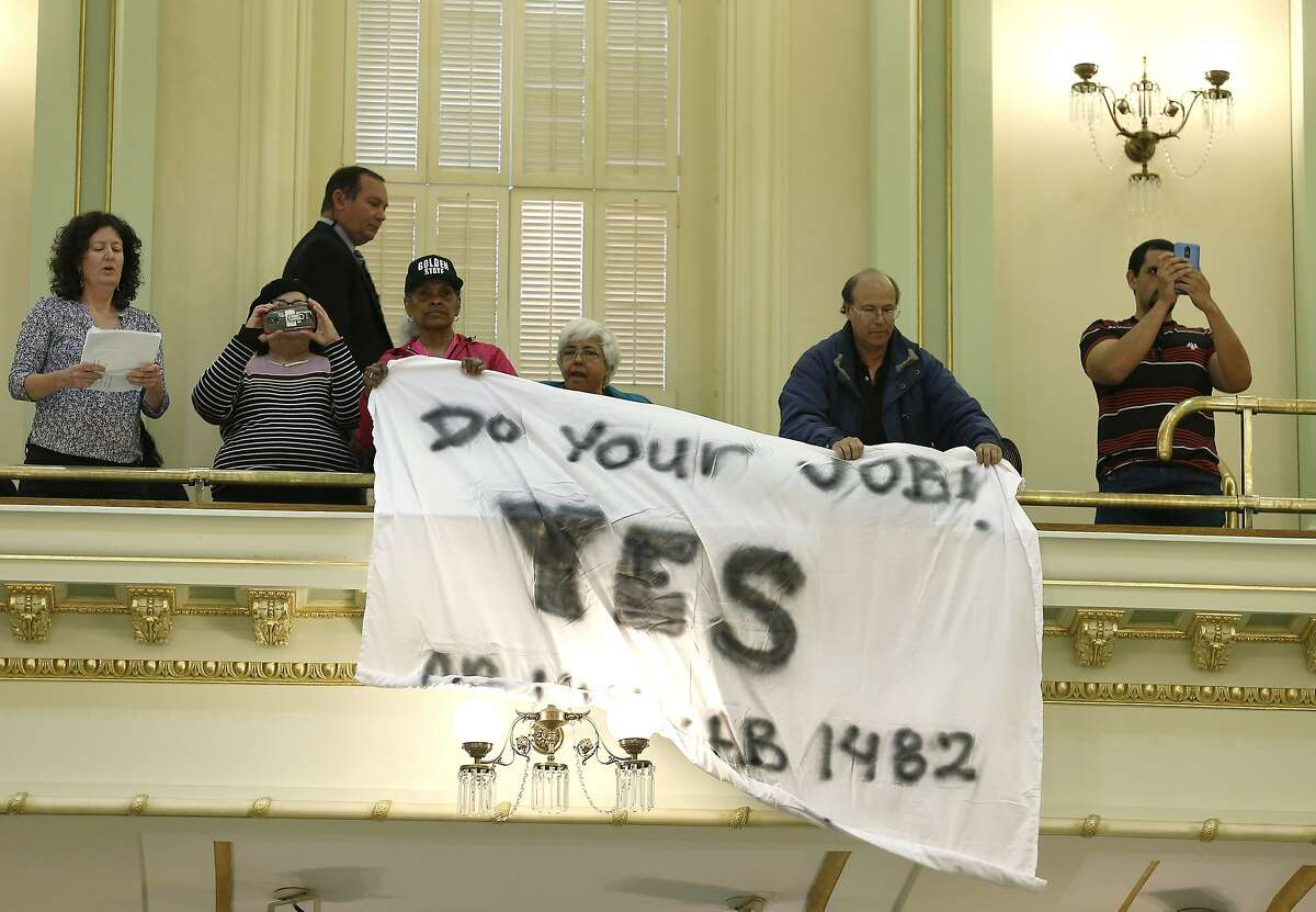 FILE - In this Wednesday, May 29, 2019 file photo, demonstrators hang a banner from the gallery of the Assembly Chambers calling for passage of a bill capping rent increases, in Sacramento, Calif. Lawmakers approved the bill Assembly Bill 1482, by Assemblyman David Chiu, D-San Francisco, that was one of the priorities of Democrats in this year's legislative session that ended Friday, Sept. 13. (AP Photo/Rich Pedroncelli, File)