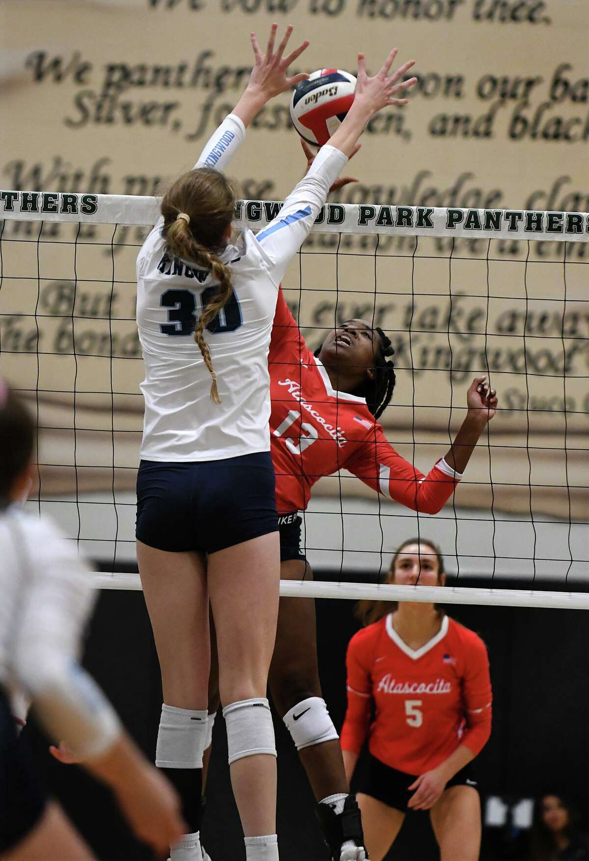 Atascocita senior outside hitter Zaire Miles (13) gets blocked by Kingwood junior middle blocker Megan Wilson (30) during the first set of their District 22-6A matchup at Kingwood Park High School on Oct. 1, 2019.