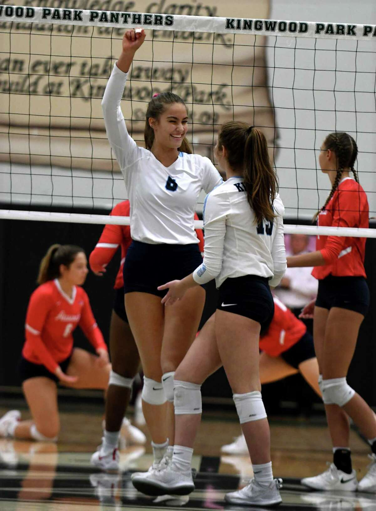Kingwood sophomore middle blocker Sophie Ocampo, left, celebrates a point against Atascocita with teammate and sophomore setter Sydney Hicks during the first set of their District 22-6A matchup at Kingwood Park High School on Oct. 1, 2019.