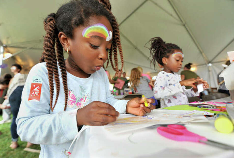 Elornam Kraka, 4, of Edwardsville (foreground) and her sister Edinam, 6, work on their art projects in the main tent Saturday at City Park.  Photo: Thomas Turney | For The Telegraph