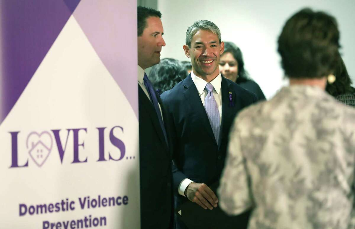 """Mayor Ron Nirenberg, center, City Manager Erik Walsh, left, and Assistant City Manager Colleen Brider, right, chat before the City of San Antonio unveiled a new public service campaign called """"Love Is..."""", to raise awareness about domestic violence locally."""