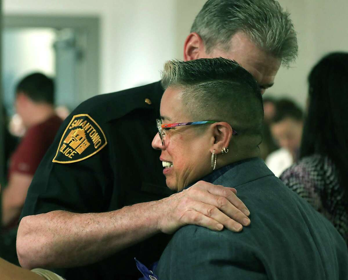 """San Antonio Police Chief William McManus chats with Judge Rosie Gonzalez as the city unveils a new campaign of public service announcements called """"Love Is..."""", to raise awareness about domestic violence locally."""