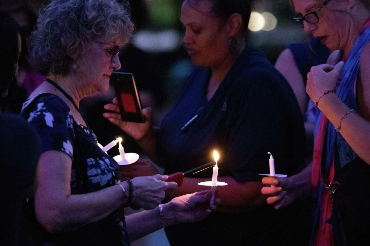 Participants light candles during the Houston Area Women's Center candle-lit vigil at City Hall to raise awareness about domestic violence Monday, Sep 30, 2019, in Houston.