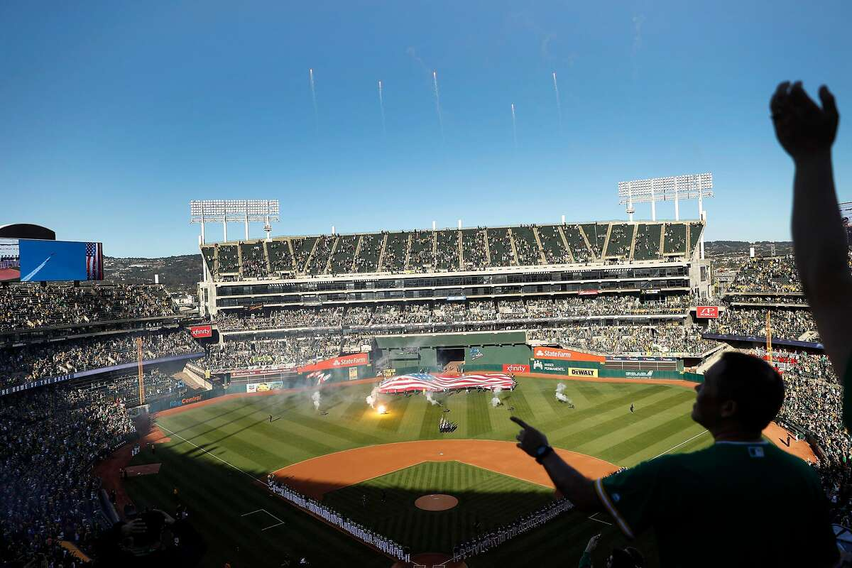 Fans cheer a flyover during National Anthem before Oakland Athletics play Tampa Bay Rays in American League Wild Card game at Oakland Coliseum in Oakland, Calif., on Wednesday, October 2, 2019.