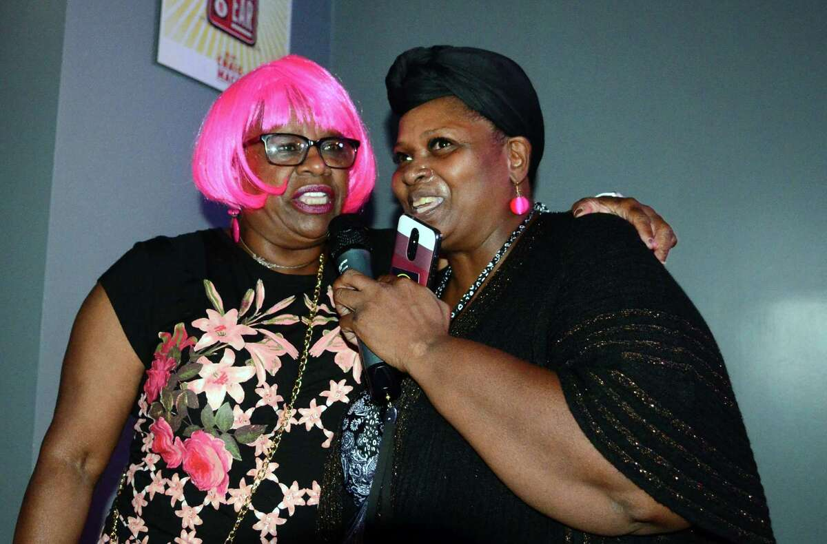 Senator Marilyn Moore, left, sings with supporter Wanda Simmons during a fundraiser for her new write-in mayoral campaign at Blvd Karaoke in Bridgeport, Conn., on Wednesday Oct. 2, 2019.
