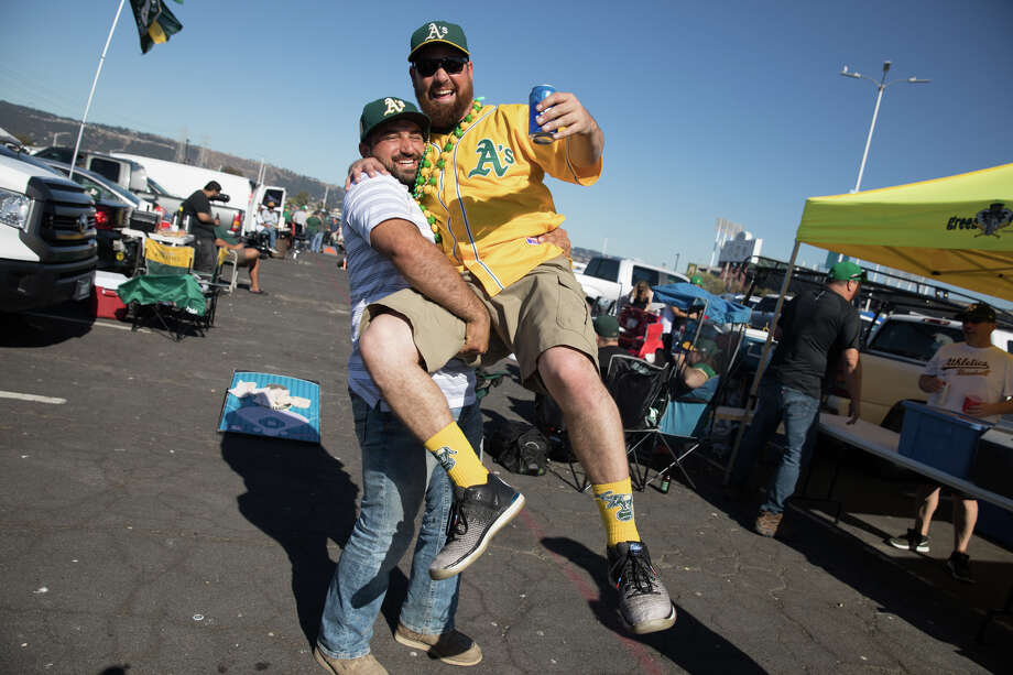 Abraham Navarro is hosted up by friend Mike Castillo. A's fans tailgated  before the Oakland A's took on the Tampa Bay Rays in the AL Wild Card  Game at the RingCentral Coliseum in Oakland, California on Oct. 2, 2019. Photo: Douglas Zimmerman/SFGate.com / SFGate.com