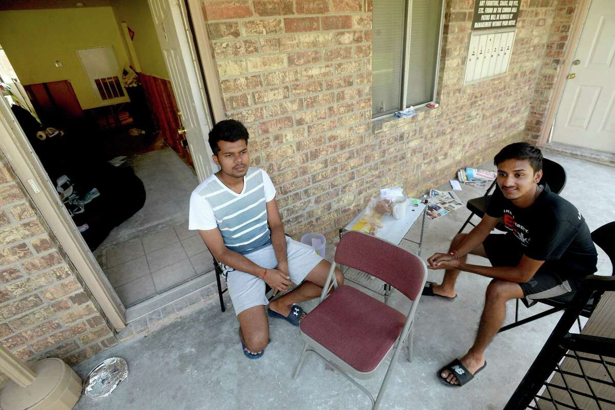 International students Dhruvik Patel (left) and Darshan Modh sit at their make-shift dining table outside their gutted first floor apartment at University Apartments. The pair are making due while trying to juggle school and daily life in the wake of Imelda. Modh says he was in Texas just a month before the flood hit, and the impact is something he's never experienced before. Photo taken Wednesday, October 02, 2019 Kim Brent/The Enterprise