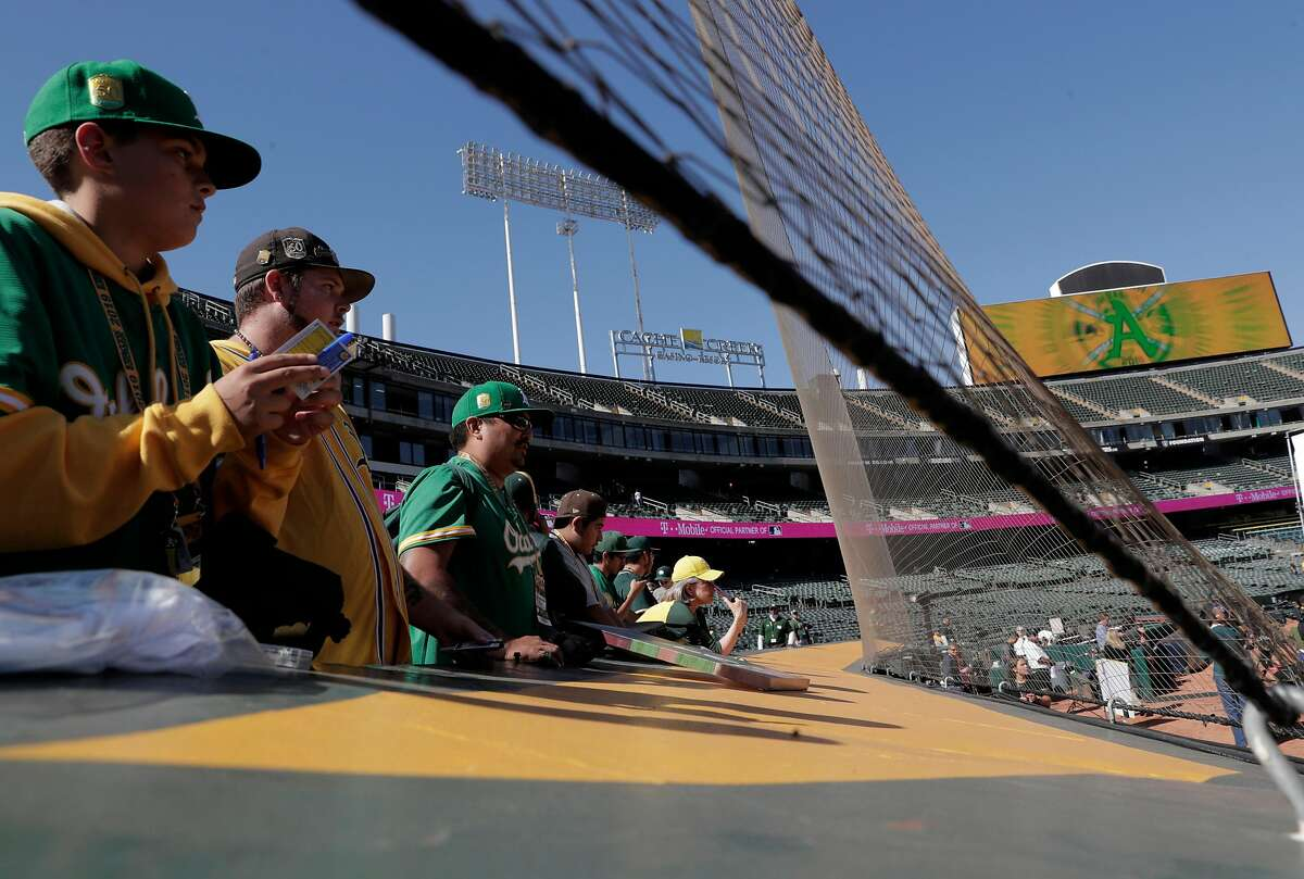 Oakland A's fans watch the team warm up before the Oakland Athletics played the Tampa Bay Rays at the Oakland Coliseum in the Wild Card playoff game in Oakland, Calif., on Wednesday, October 2, 2019.