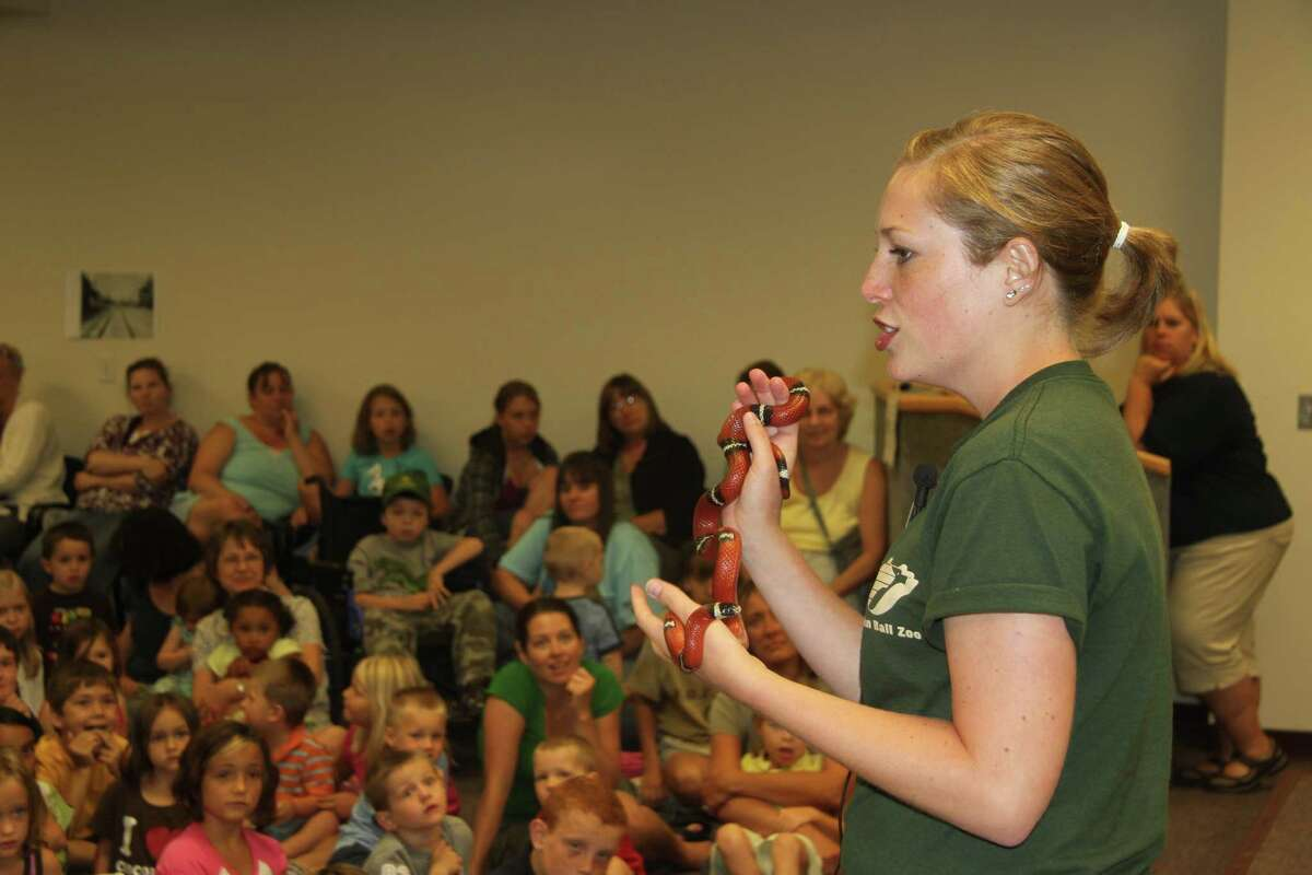 MILK SNAKE: Animal handler Claire Victory from the John Ball Zoo in Grand Rapids shows off a non-venomous milk snake. Nearly 300 people attended an event on Wednesday at city hall.