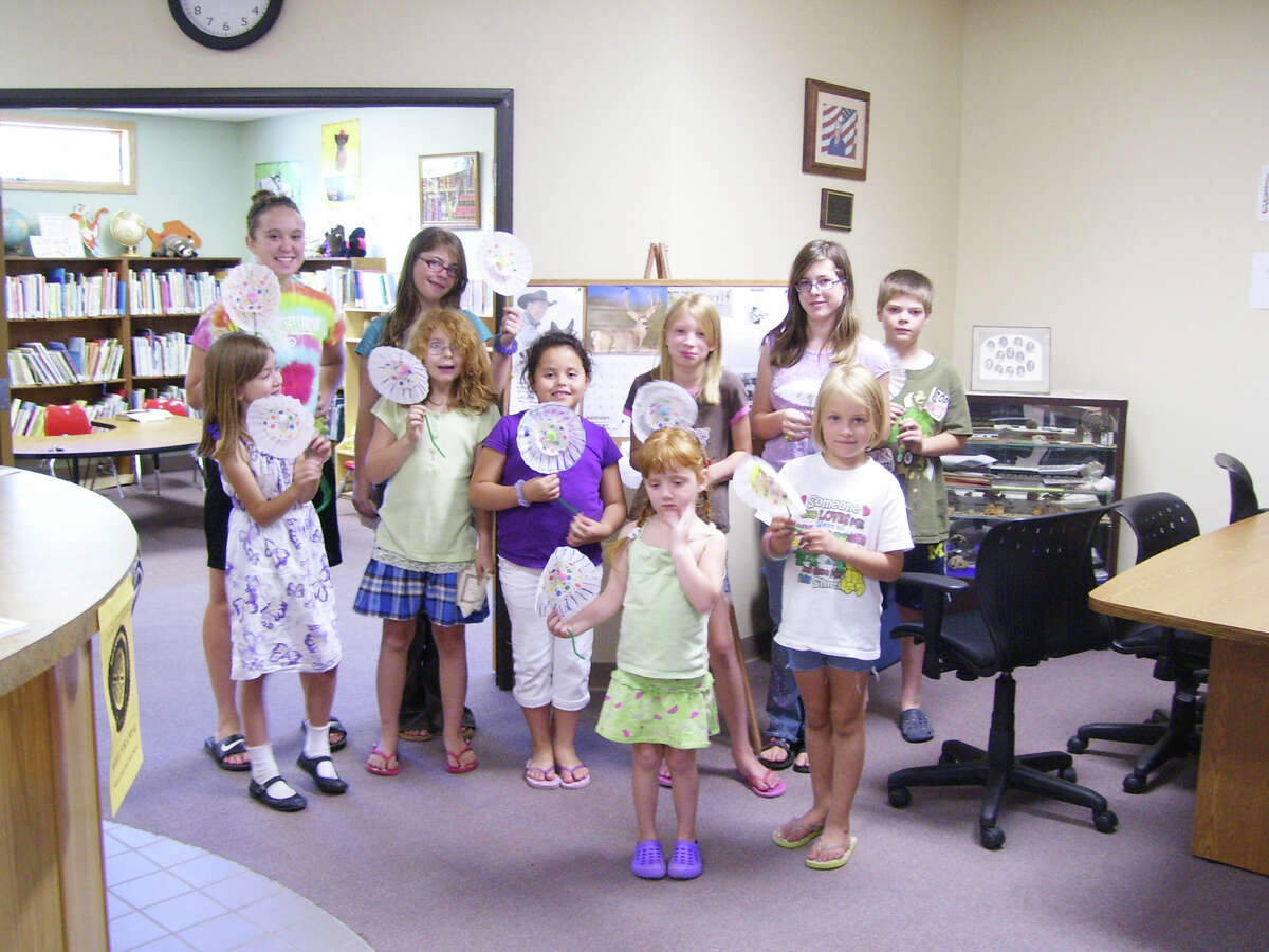 """FLOWER POWER: Children at the Wheatland Township Library made flowers and danced to the """"Tooty Ta"""" song, which has become a favorite at the library. (Courtesy photo)"""