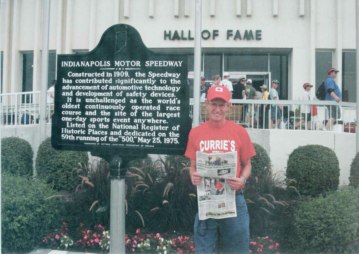 SPEED: Bruce Parker, of Big Rapids, was at the Indianapolis Motor Speedway on July 31 for the Brickyard 400 race. Here, he takes time to read the Pioneer. Behind him is the Indianapolis Motor Speedway Hall of Fame. (Courtesy photo)