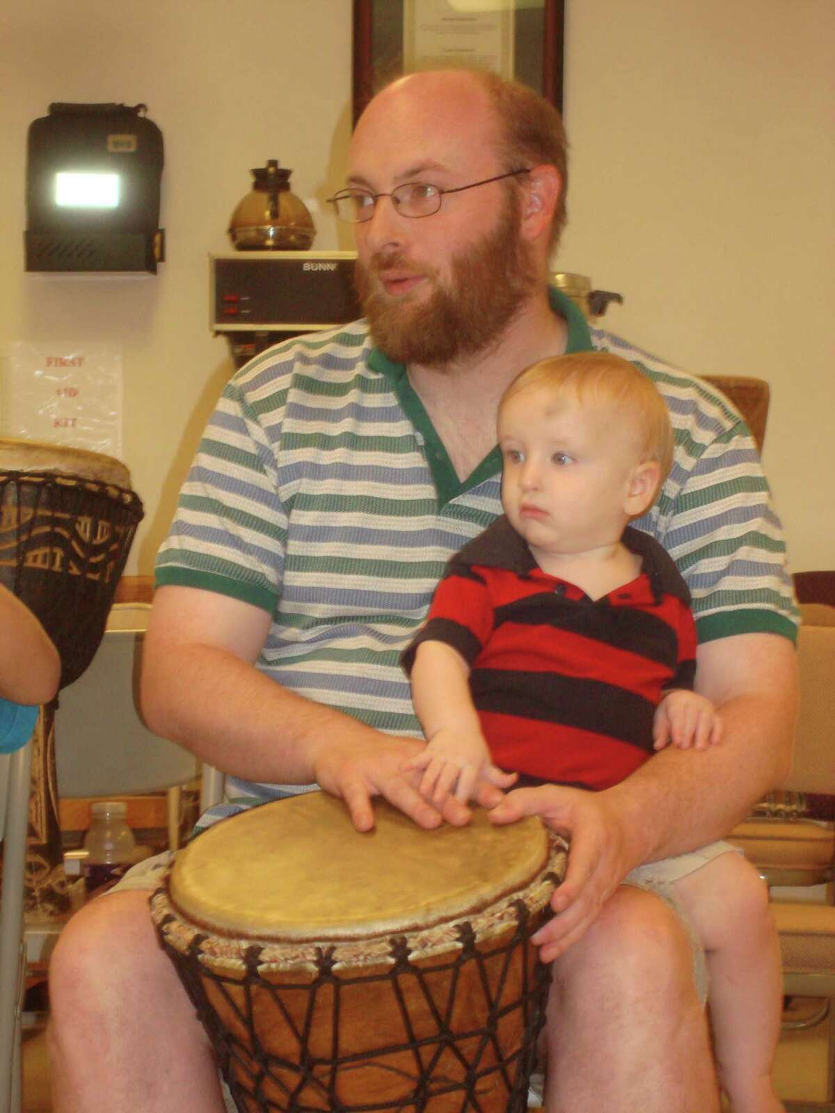 """LIKE FATHER, LIKE SON: Lee Johnson and his son, Gideon, were two of the more than 40 people to participate in the """"Drummunity"""" event on Thursday hosted by the Big Rapids Community Library. The event was the last of the library's summer reading programs."""