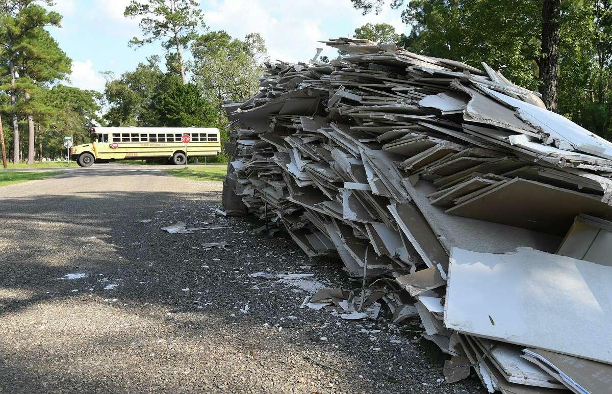 A Hardin-Jefferson school bus passes a pile of sheetrock in front of a Bevil Oaks home on Wednesday. Photo taken Wednesday, 10/2/19