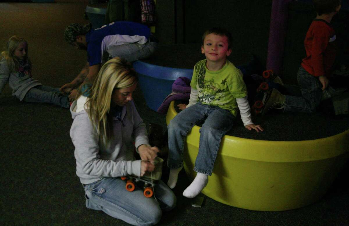 READY TO SKATE: Rachel Haner-Allers helps her son, Willy Allers, get his skates on at Family Night.