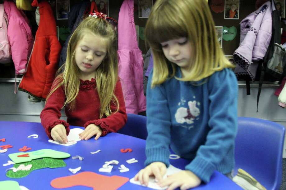 STOCKINGS: Preschoolers Sophie Micky (left) and Sela Guiney decorate stockings and Christmas cards in Tisha Kwant's class at St. Mary Catholic School. (Pioneer photos/Lauren Fitch)
