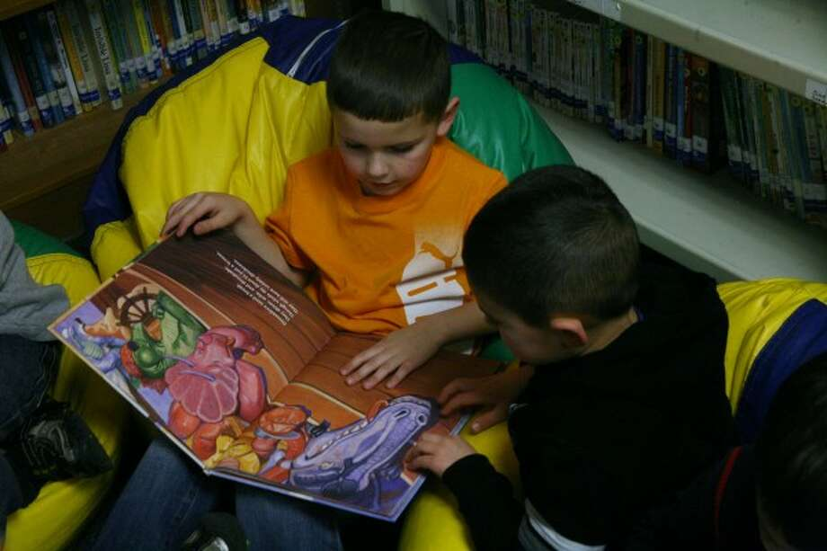 STORY HOUR: Brookside students in Laura Macias' Young 5's class spend time reading in the library during their first day back at school after winter break.