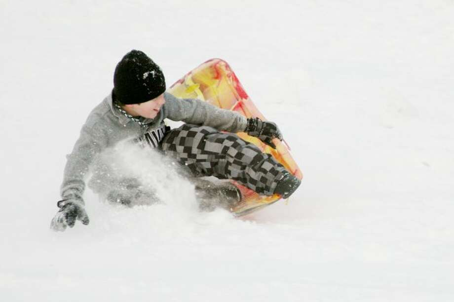 WHITE OUT: Elliot Seay, a fifth-grader at Big Rapids Middle School, slides down the hill of snow at Crossroads Charter Academy's parking lot on Saturday. (Pioneer photos/Lauren Fitch)