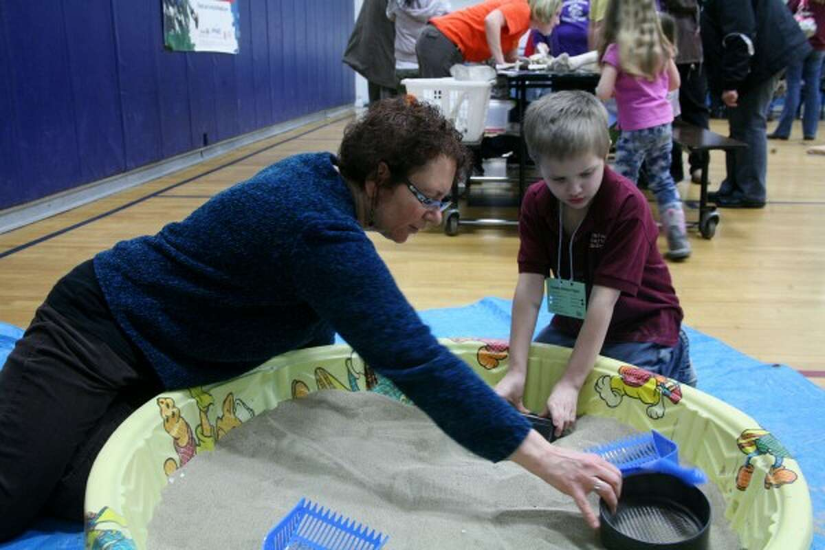 BURIED TREASURE: Students stopped by the paleontology station at Crossroads' second annual Family Science Night.