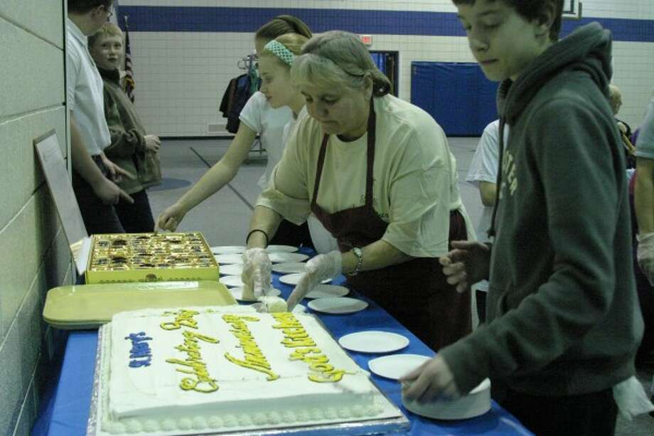 CAKE: Volunteers cut and serve slices of cake to attendees of the weekly God's Kitchen meal on Tuesday. The Catholic ministry celebrated its second anniversary with a special prayer prior to the meal led by Father Lam Le.