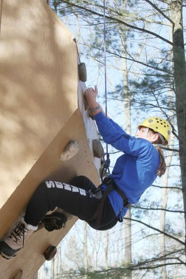 """CLIMBING WALL: A climber works her way up the """"difficult"""" side of the climbing wall at Cran-Hill Ranch in Rodney. More than 500 people attended the ranch's annual Winterfest on Saturday."""
