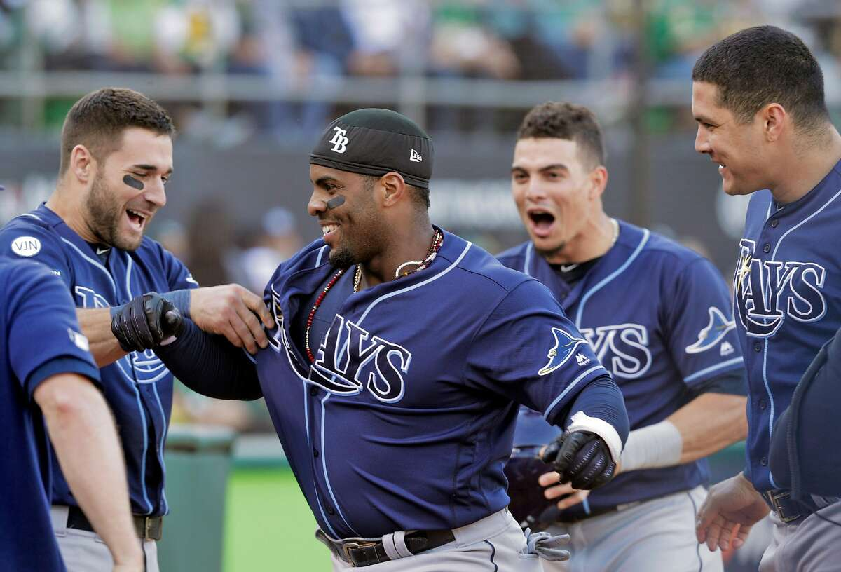 Yandy Diaz (2) is congratulated by teammates in the dugout after hitting a solo homerun in the first inning as the Oakland Athletics played the Tampa Bay Rays at the Oakland Coliseum in the AL Wild Card playoff game in Oakland, Calif., on Wednesday, October 2, 2019.
