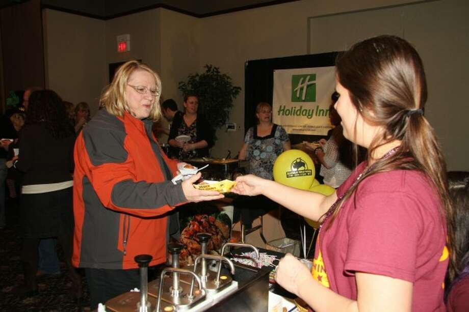 TASTE OF MECOSTA: Mary Ann Lenon, director of the Morton Township Library, gets a basket of chicken from the Buffalo Wild Wings table at the 2012 Taste of Mecosta on Fat Tuesday at the Holiday Inn in Big Rapids.