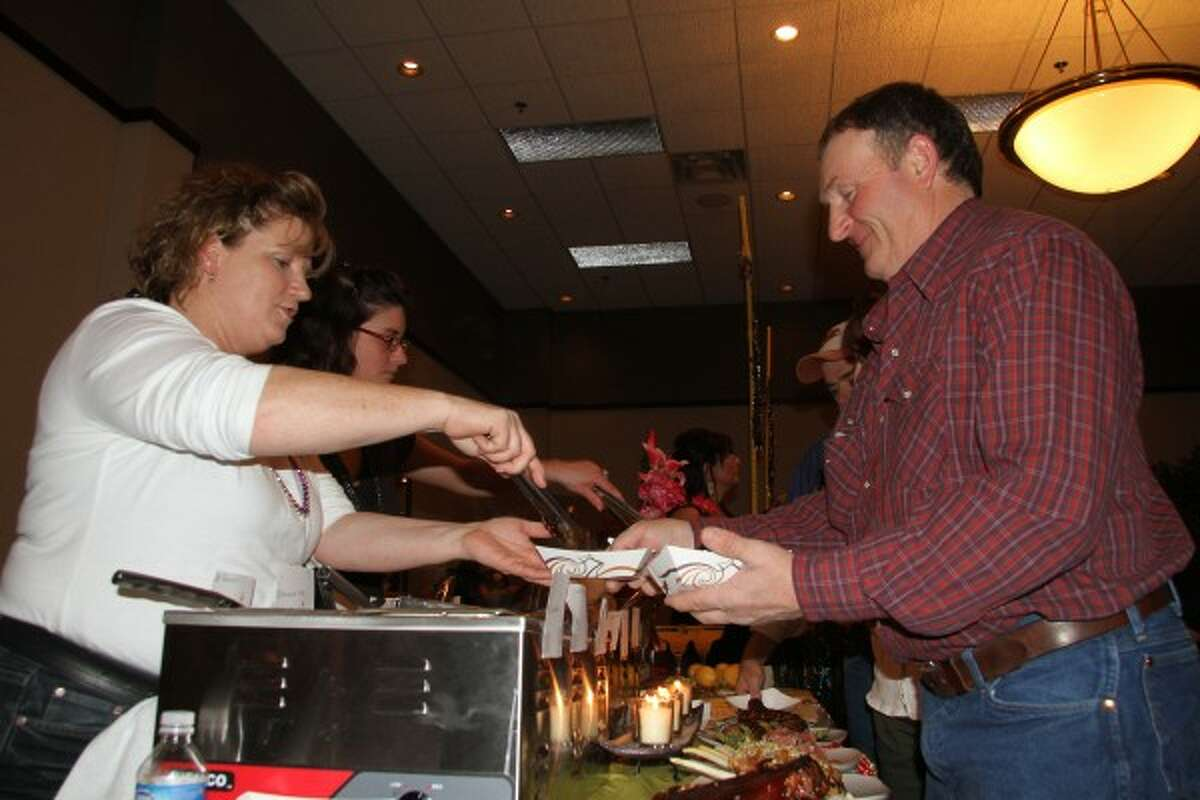 FINGER LICKIN' GOOD: Jules Manley (left), of Gregory's Grille, serves a basket of chicken to Brent Bazaire, of Barryton, during the annual Taste of Mecosta.